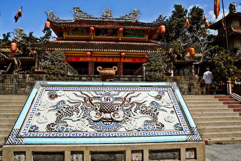 Exterior view of the reconstructed Long Son Pagoda in Nha Trang, including the mosaic panel in front with the protective dragon.  One tourist (man) in shorts at the top of the approach stairs, looking around.