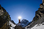 Hiker Grant Ordelheide stands on a rock and reaches for the afternoon sun in Garnet Canyon below Middle Teton in Grand Teton National Park, Wyoming