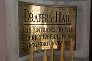 The entrance plaque of Drapers' Hall livery company in Throgmorton Street, on 17th Juy 2017, in the City of London, England. The Drapers' Company is a Livery Company in the City of London whose roots go back to the 13th century, when as its name indicates, it was involved in the drapery trade. While it is no longer involved in the trade, the Company has evolved acquiring a new relevance. Its main role today is to be the trustee of the charitable trusts that have been left in its care over the centuries. The Company also manages a thriving hospitality business. The first Drapers' Hall was built in the 15th century in St Swithin's Lane.  It bought a Hall on the present site in Throgmorton Street in 1543 from King Henry VIII for £1,200 (about £350,000 in today's money). The Hall that the Company purchased from King Henry VIII in 1543 had been the private residence of Thomas Cromwell, Earl of Essex until his execution in 1540, when it was confiscated by the Crown.