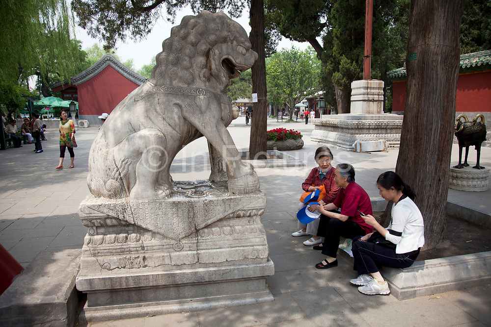 Elderly women come to chat together next to a stone lion in Beihai Park. Beihai Park is an imperial garden in Beijing. First built in the 10th century, it is amongst the largest of Chinese gardens, and contains numerous historically important structures, palaces and temples. Since 1925, the place has been open to the public as a park. It is also connected at the south to the Shichahai. The Park has an area of more than 69 hectares, with a lake that covers more than half of the entire Park.