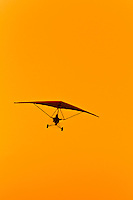 An ultralight flies at sunset on the Skeleton Coast, Swakopmund, (the Atlantic Ocean off of the Namib Desert coastline), Namibia