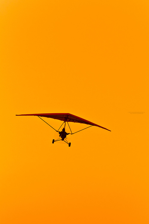 An ultralight flies at sunset on the Skeleton Coast, Swakopmund, (the Atlantic Ocean off of the Namib Desert coastline), Namibia