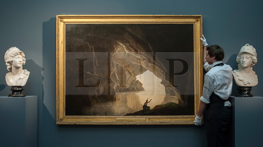 """© Licensed to London News Pictures. 04/12/2015. London, UK. A technician presents """"A grotto in the Gulf of Salerno, with the figure of Julia, banished from Rome"""" by Joseph Wright of Derby (est. £100,000-150,000), ahead of Sotheby's London evening sale of Old Master and British paintings on 9th December 2015. This is the last official image of his reign.  Photo credit : Stephen Chung/LNP"""