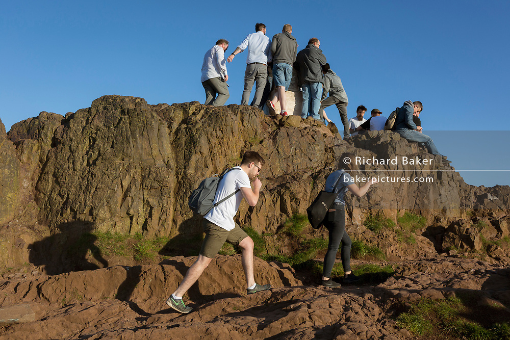 """In summer evening sunshine, walkers climb the last metres to the summit of Arthur's Seat in Holyrood Park that overlooks the city of Edinburgh, on 26th June 2019, in Edinburgh, Scotland. Arthur's Seat is an extinct volcano which is considered the main peak of the group of hills in Edinburgh, Scotland, which form most of Holyrood Park, described by Robert Louis Stevenson as """"a hill for magnitude, a mountain in virtue of its bold design"""". The hill rises above the city to a height of 250.5 m (822 ft), providing excellent panoramic views of the city and beyond."""