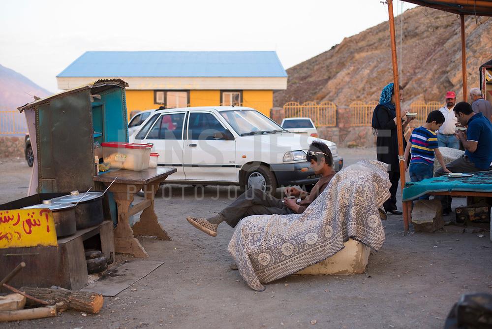 Iran, Dizin, 12.08.2016: Rastplatz nahe Dizin im Alborz-Gebirge. Ein Asch-Verkäufer bei seiner Teepause. Ash Reshteh, persischer Eintopf.
