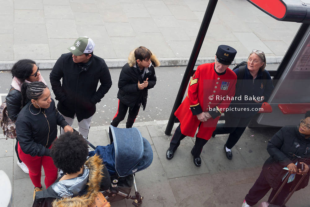 The public stand next to an elderly Chelsea Pensioner at a bus stop on Westminster Bridge, in Lambeth, on 28th March 2019, in London, England