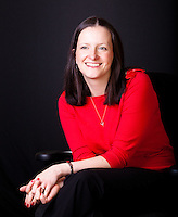 Corporate portrait seated young business woman wearing red shot against black background