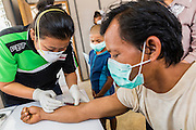 03 MARCH 2104 - MAE KASA, TAK, THAILAND: A medic takes a blood draw on the husband of a tuberculosis patient at the Sanatorium Center for Border Communities in Mae Kasa, about 30 minutes north of Mae Sot, Thailand. So far the man has tested negative for TB. The Sanatorium provides treatment and housing for people with tuberculosis in an isolated setting for about 68 patients, all Burmese. The clinic is operated by the Shoklo Malaria Research Unit and works with several other NGOs that assist Burmese people in Thailand. Reforms in Myanmar have alllowed NGOs to operate in Myanmar, as a result many NGOs are shifting resources to operations in Myanmar, leaving Burmese migrants and refugees in Thailand vulnerable. Funding cuts could jeopardize programs at the clinic. TB is a serious health challenge in Burma, which has one of the highest rates of TB in the world. The TB rate in Thailand is ¼ to ⅕ the rate in Burma.        PHOTO BY JACK KURTZ