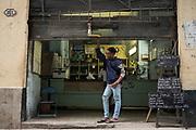 A shop worker observes who passes by, in Havana, Cuba.