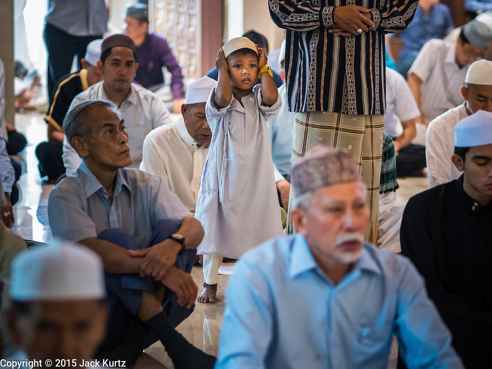 17 JULY 2015 - BANGKOK, THAILAND:     A boy prays in Ton Son Mosque during services marking Eid al-Fitr. Eid al-Fitr is also called Feast of Breaking the Fast, the Sugar Feast, Bayram (Bajram), the Sweet Festival or Hari Raya Puasa and the Lesser Eid. It is an important Muslim religious holiday that marks the end of Ramadan, the Islamic holy month of fasting. Muslims are not allowed to fast on Eid. The holiday celebrates the conclusion of the 29 or 30 days of dawn-to-sunset fasting Muslims do during the month of Ramadan. Islam is the second largest religion in Thailand. Government sources say about 5% of Thais are Muslim, many in the Muslim community say the number is closer to 10%.          PHOTO BY JACK KURTZ