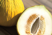 Close up photo of a couple Casaba melons sitting on a rustic wood deck with one cut open