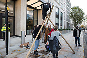 Environmental activists from Extinction Rebellion erect a tripod outside the Shell Centre on the 25th anniversary of the killings of the Ogoni Nine on 10 November 2020 in London, United Kingdom. The Ogoni Nine, leaders of the Movement for the Survival of the Ogoni People (MOSOP) including activist Ken Saro-Wiwa, were executed by the Nigerian government in 1995 after having led a series of peaceful marches involving an estimated 300,000 Ogoni people against the environmental degradation of the land and waters of Ogoniland by Shell and to demand both a share of oil revenue and greater political autonomy.
