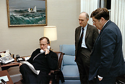 United States President George H.W. Bush, left, speaks on the telephone from the White House in Washington, DC on December 20, 1989 as National Security Advisor Brent Scowcroft, center, and White House Chief of Staff John Sununu, right, look on.<br /> Photo by Carol T. Powers / White House via CNP/ABACAPRESS.COM