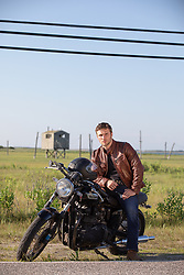 hot guy sitting on a motorcycle on a rural road