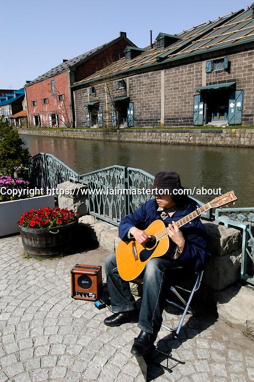 Busker playing guitar beside canal in historic Otaru on Hokkaido island in Japan