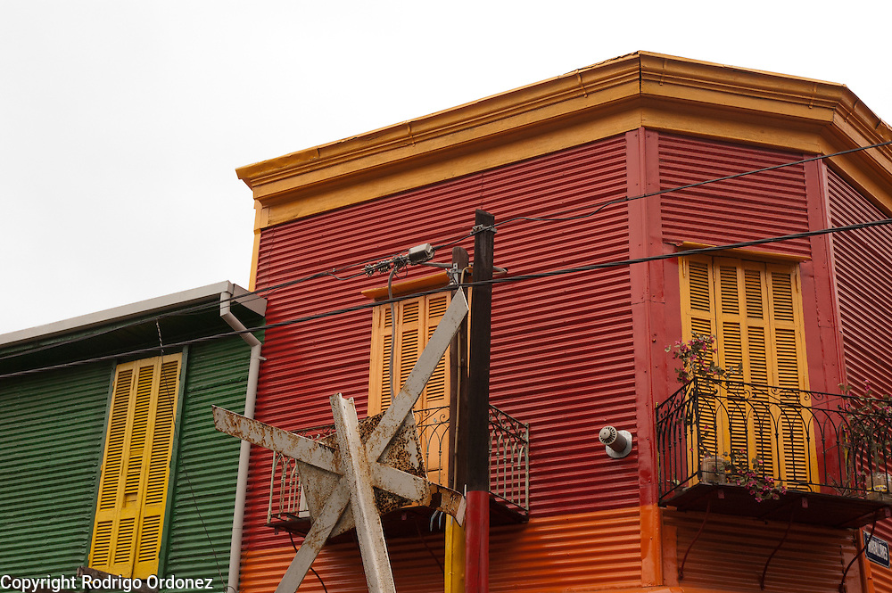 General view of houses in Caminito street, in La Boca neighborhood of Buenos Aires, Argentina.<br /> Caminito is a pedestrian street created in the late 1950s by local painter Benito Quinquela Martín and other artist friends to recreate a version of the old immigrant neighborhood of La Boca, using wood and corrugated zinc painted in bright colors. Today, Caminito and the surrounding areas feature cafes, souvenir shops, tango dancers and other street performances aimed to attract tourists.
