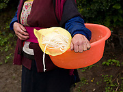 A Tibetan woman carries an orange plastic bowl and a yellow carrier bag containing rice noodles which she has just purchased from a mobile shop in a village near Zongdian (Shangri-La), Yunnan province, China