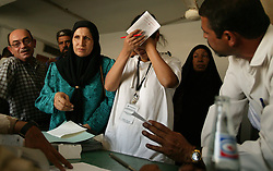 Alyaa Abdul Hassan Abbood, 23, a translator, is overcome with frustration as she tries to mediate as Iraqi civilians crowd into the courtroom to receive monetary compensation for damages done by American troops in Baghdad, Iraq, Sept. 27, 2003.