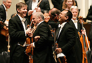 Daniel Barenboim, left, takes Chicago Symphony Orchestra concertmaster Robert Chen, right, and assistant concertmaster David Taylor off the stage with him after conducting the group in Beethoven's Symphony No. 9 at Symphony Center in Chicago, Saturday, June 17, 2006. The performance was his final appearance as musical director of the orchestra. (AP)