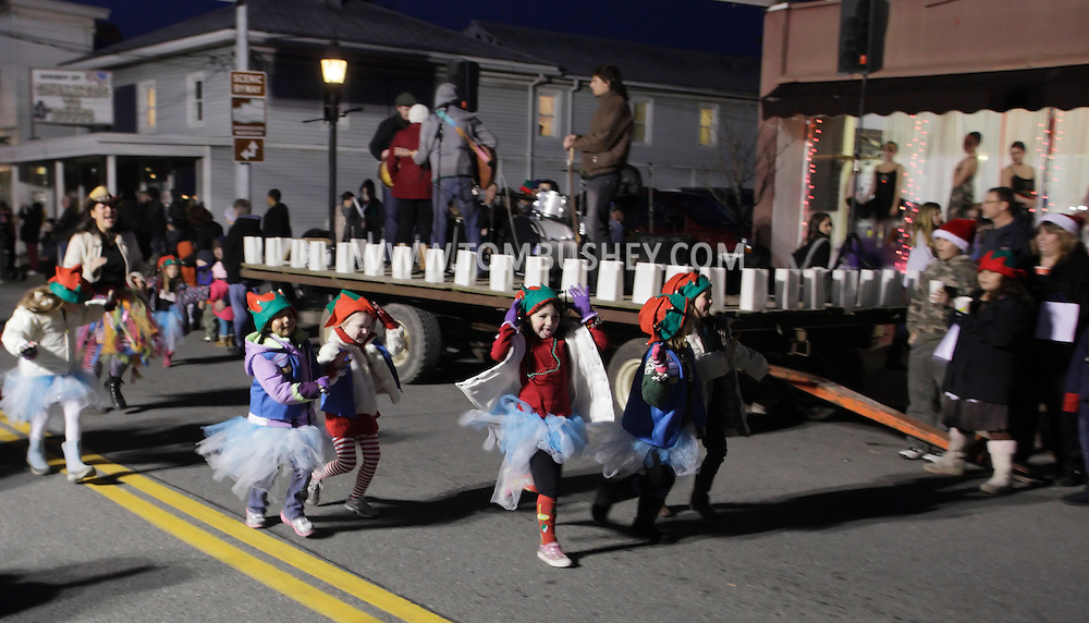 Pine Bush, New York  - Children in the parade run down Main Street as the bank Somerton Suitcase plays on the stage during A Community Country Christmas 2011on  Dec. 3, 2011.
