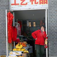 Asia, China, Beijing. Woman standing in Beijing Shop Doorway.