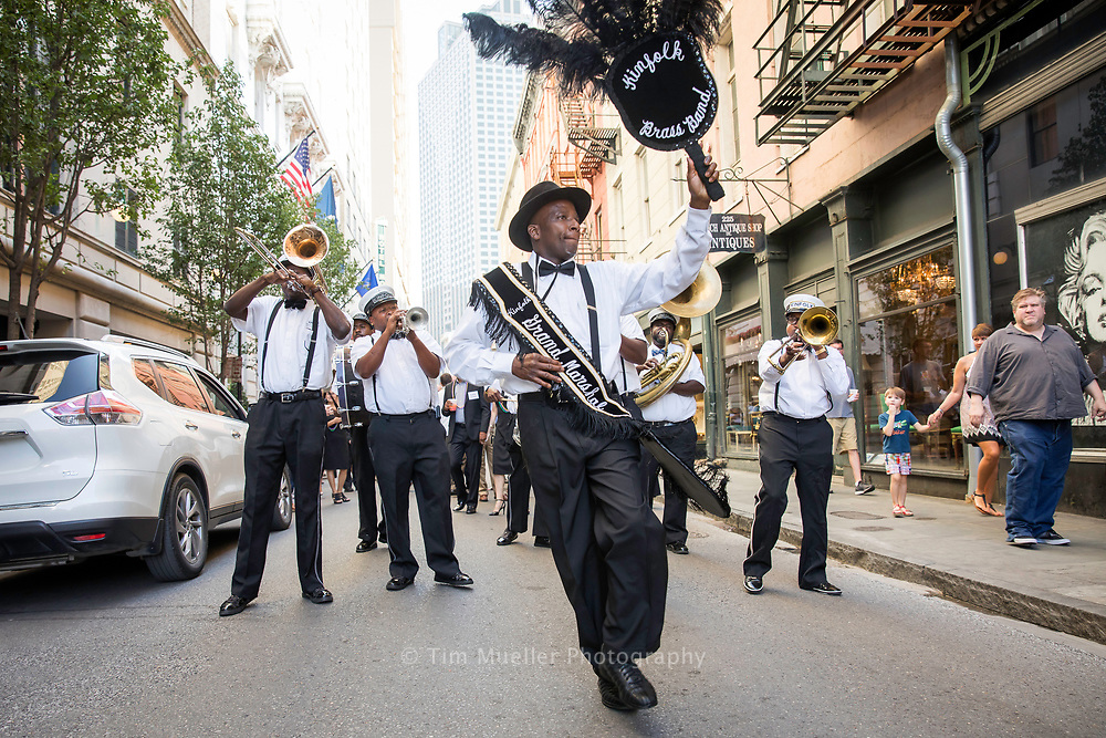The Kinfolk Brass Band leads a second-line parade down Royal Street in the New Orleans French Quarter. Founded by brothers Percy and Richard Anderson in 2005, the band performs Mardi Gras Indian chants, New Orleans funk, modern jazz, and traditional brass band sounds.