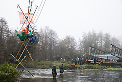 Denham, UK. 7th December, 2020. Dan Hooper, better known as roads protester Swampy during the 1990s, occupies a tripod positioned in the river Colne in order to try to delay bridge building works in connection with the HS2 high-speed rail link. Anti-HS2 activists continue to resist the controversial £106bn rail project from a series of protest camps based along its initial route between London and Birmingham.