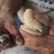 Tommy Coates carves walrus ivory into a snowy owl figurine. Barrow, Alaska