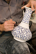 "Closeup of a traditional blue flower design being applied to a bisqueware vase at Morvarid (Pearl) Pottery Factory, Meybod,  Iran. (Also spelled ""Maybod""). Painters there each has his own design assignment, often working with others applying their own elements on a single piece."