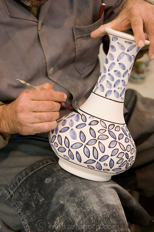 """Closeup of a traditional blue flower design being applied to a bisqueware vase at Morvarid (Pearl) Pottery Factory, Meybod,  Iran. (Also spelled """"Maybod""""). Painters there each has his own design assignment, often working with others applying their own elements on a single piece."""