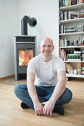 Portrait of man sitting in his living room with fireplace, smiling