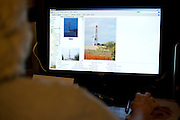 Debbie Ingram flips through photos on her computer of a gas well that sits 385 feet from her home and was last fracked in March on July 22, 2014 in Argyle, Texas. (Cooper Neill for The Texas Tribune)
