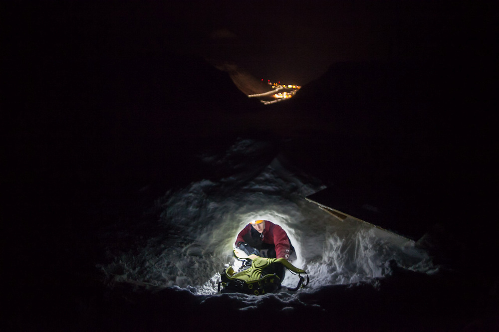 Stephen Jennings crawls out of an ice cave on Larsbreen, Svalbard. The lights of nearby Longyearbyen are visible in the distance.