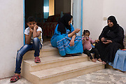 A moderately wealthy Egyptian family of different ages sit on their courtyard steps of their home in the village of Bairat, on the West Bank of Luxor, Nile Valley, Egypt.