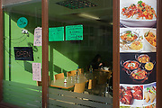 Vegetarian balti restaurant menu window on Brick Lane in East London, home to many Indian-style curry houses and businesses. A lone diner eats in shadows towards the rear of the restaurant and illustrations of the dishes offered here are on the corner of the business' window. Vegetarian suggestions and prices are also advertised in Brick Lane, a street in the London Borough of Tower Hamlets. It runs from Swanfield Street in the northern part of Bethnal Green, crosses Bethnal Green Road, passes through Spitalfields and is linked to Whitechapel High Street to the south by the short stretch of Osborn Street. Today, it is the heart of the city's Bangladeshi-Sylheti community and is known to some as Banglatown.
