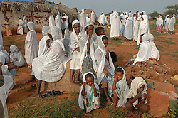"""Coptic christians pray outside St. Mary's church in the village of Fithi which means """"justice"""" on the outskirts of  Barentu, Eritrea August 27, 2006. During this ceremony, Tiblits neighbor Zaid Tesheme, 31 had her baby baptized with the name Mihreteab. The donkey that Tiblets received from the womens union """"Hamade"""", helped them prepare for the celebration afterwards.   (Photo by Ami Vitale)"""