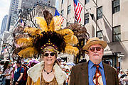 New York, NY - April 16, 2017. A couple at New York's annual Easter Bonnet Parade and Festival on Fifth Avenue. She is wearing an elaborate hat with yellow and brown plumes.