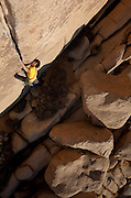 Brenton Reagan, an Exum Mountain Guide leads Hot Rocks, a 5.11C trad route, on excellent granite rock in Joshua Tree National Park, California. USA