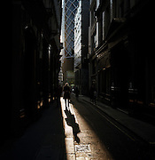 A businessman walks through late afternoon sunlight in a narrow lane in the City of London, the heart of the capital's financial district.