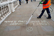 A City of Westminster cleaner jet washes away chalk based graffiti stating When Politicians Lie Democracy Dies, outside the Cabinet Office in Whitehall as Ministers hold a Brexit Cabinet meeting on 16th August 2019 in London, United Kingdom.