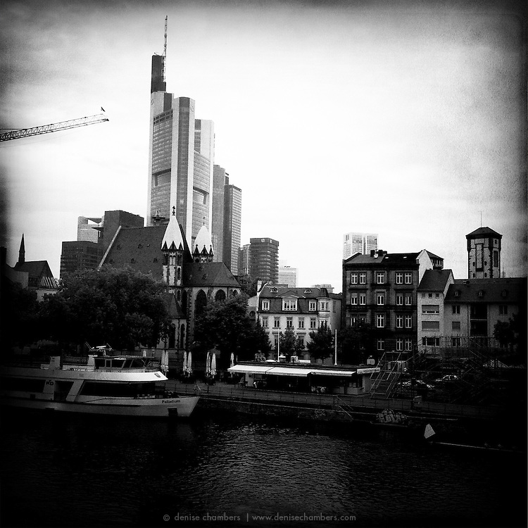 Modern skyscrapers tower over historic buildings along the river in Frankfurt am Main