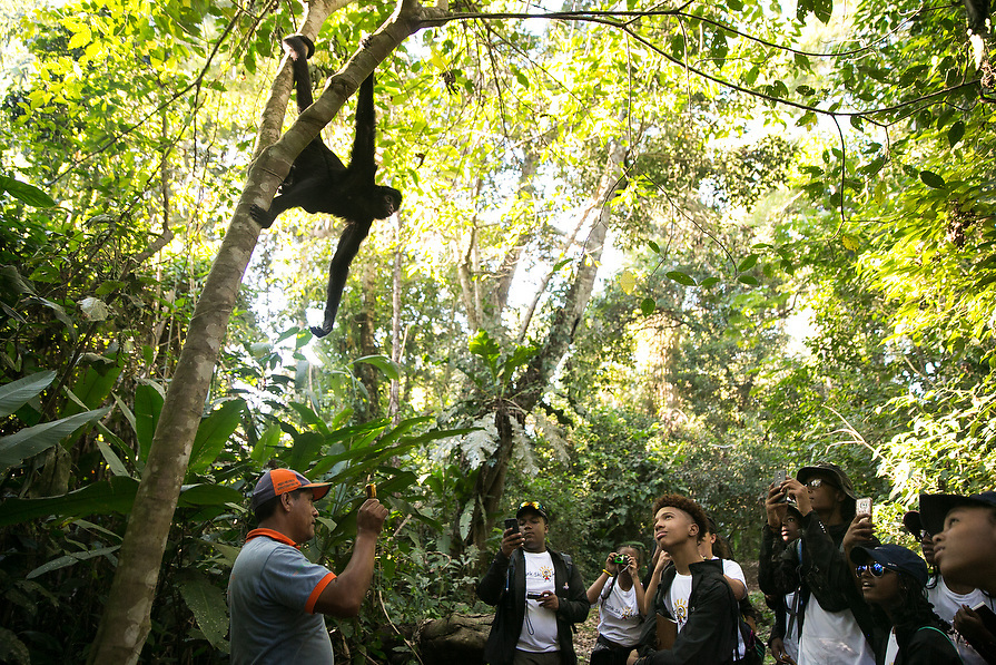 Tour guide, Urbano Huaman shows the kids how to feed wild monkeys.