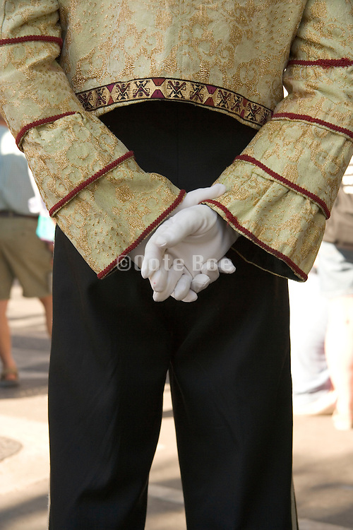man standing hands clasped behind his back with white gloves on