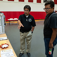 Albert Calamity Sr., 50, talks with Chase Bebo, 22, about some of the programs the Office of Special Education & Rehabilitation Services held in the Wellness Center at the NTU campus for the Career Fair in Crownpoint on Thursday.