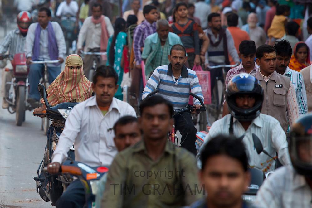 Muslim woman in crowded street scene during holy Festival of Shivaratri in city of Varanasi, Benares, Northern India
