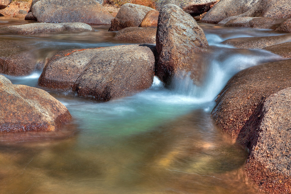 a gently flowing river with tumbling stones and tiny waterfalls abound in Tuolumne meadows, yosemite national park.