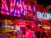 """27 FEBRUARY 2019 - BANGKOK, THAILAND: Tourists walk past Shark and Baccara, two of Bangkok's better known """"go-go"""" bars on Soi Cowboy. Bangkok, a city of about 14 million, is famous for its raucous nightlife. But Bangkok's real nightlife is seen in its markets and street stalls, many of which are open through the night.        PHOTO BY JACK KURTZ"""