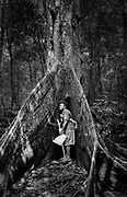 Embera guide Juancito embraces a giant tree along the Rio Sambu, Darien Province, Panama.