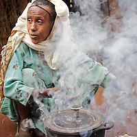 Belaynesh cooks breakfast for her neice and herself outside their home in the village of Amba Zetegn. <br /> <br /> Belaynesh Hussen (age 50) lives with her niece Tsehaynesh Bistegn, age 10, in a thatched house in Amba Zetegn, 20km from Assosa town. She farms sorghum, maize, teff and soya, all sold through the local farmers co-operative society of which she has been a part for the past three years. This village co-op is affiliated to the Assosa Farmers Multipurpose Cooperative Union.<br /> <br /> Growing oil seeds presents challenges for the famers of Assosa in western Ethiopia. Many of the most vulnerable are forced to sell to when they cannot be guaranteed a good price for their product. Farms are often located in isolated areas which entails huge amounts of time and effort simply getting seeds to market. Many farmers do not have the resources to properly invest in their land and are tied into exploitative loan arrangements with brokers that deny them the chance to take proper control of their farms. And, as with other agricultural products, it is those agents that process the seeds into oil that secure the greatest profit, very little of which trickles down to benefit the farmer.<br /> <br /> In response to these pressures, twenty farming cooperatives have formed the Assosa Farmers Multipurpose Cooperative Union. By working together, individual farmers are able to pool their resources and squeeze out exploitative agents and brokers. The Union has sufficient capital that it can afford to wait for prices to reach a level at which it is profitable to sell seeds to market. The Union provides loans to constituent members together with training and advice to help farmers make better use of their land. And by collectively hiring vehicles through the Union, farmers need not spend so much time ferrying their produce to market. <br /> <br /> All these measures benefit farmers and have now provided the Assosa Farmers Multipurpose Cooperative Union the confidence to establish an oil-seed processing unit in the regional to