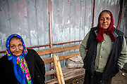 Portrait of Elena (left) and Niculina  - two Roma women waiting at a bus stop in Marginenii de Jos for getting back home from work.